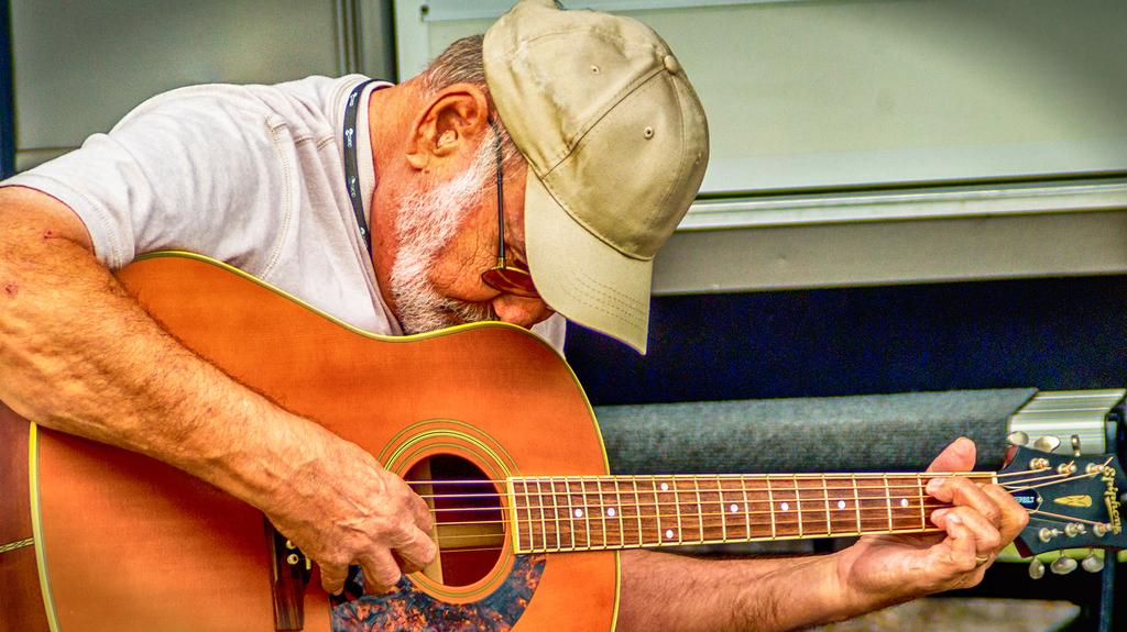 Man with cap picking guitar.