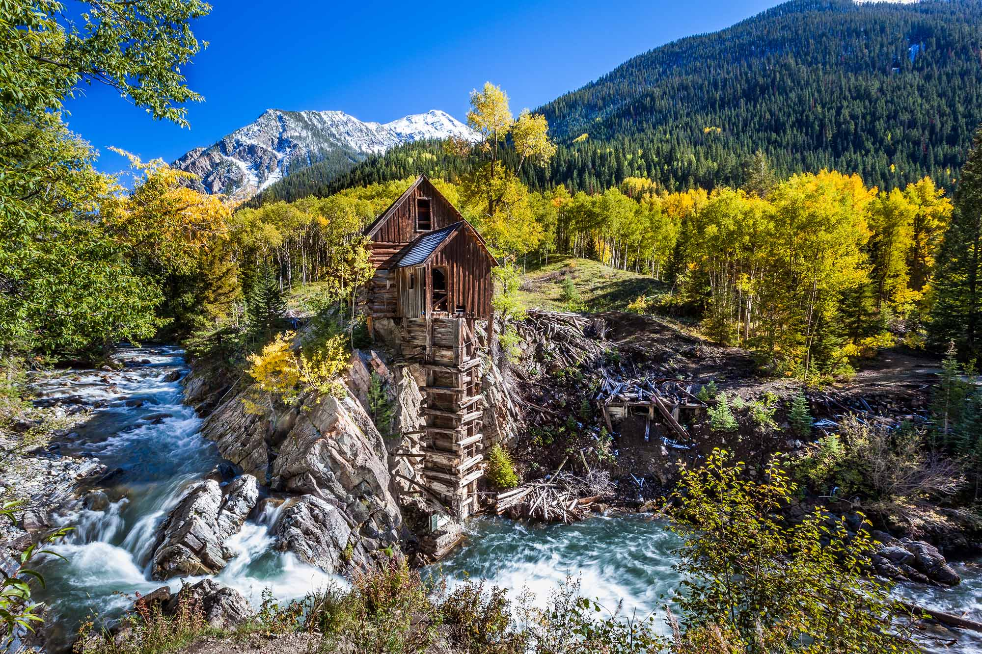 An abandoned wooden mill clings to a clifftop overlooking a churning river.