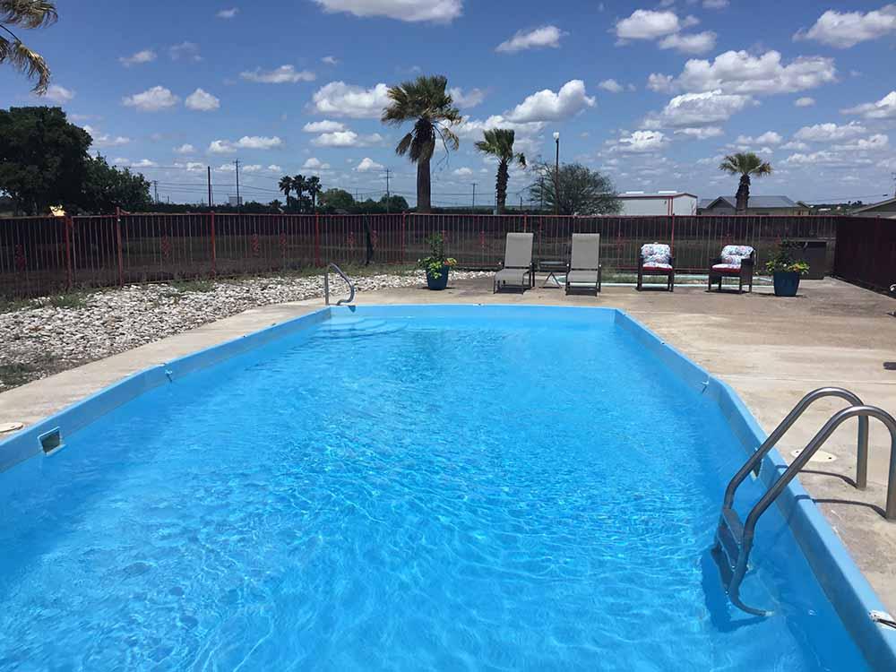 A rectangular pool under a clear Texas sky.