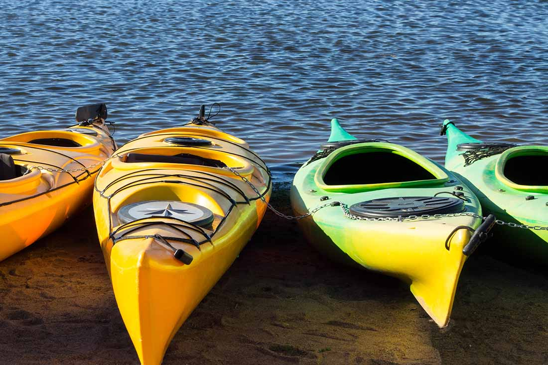 Four colorful kayaks locked with a chain facing the ocean shore in a low evening light