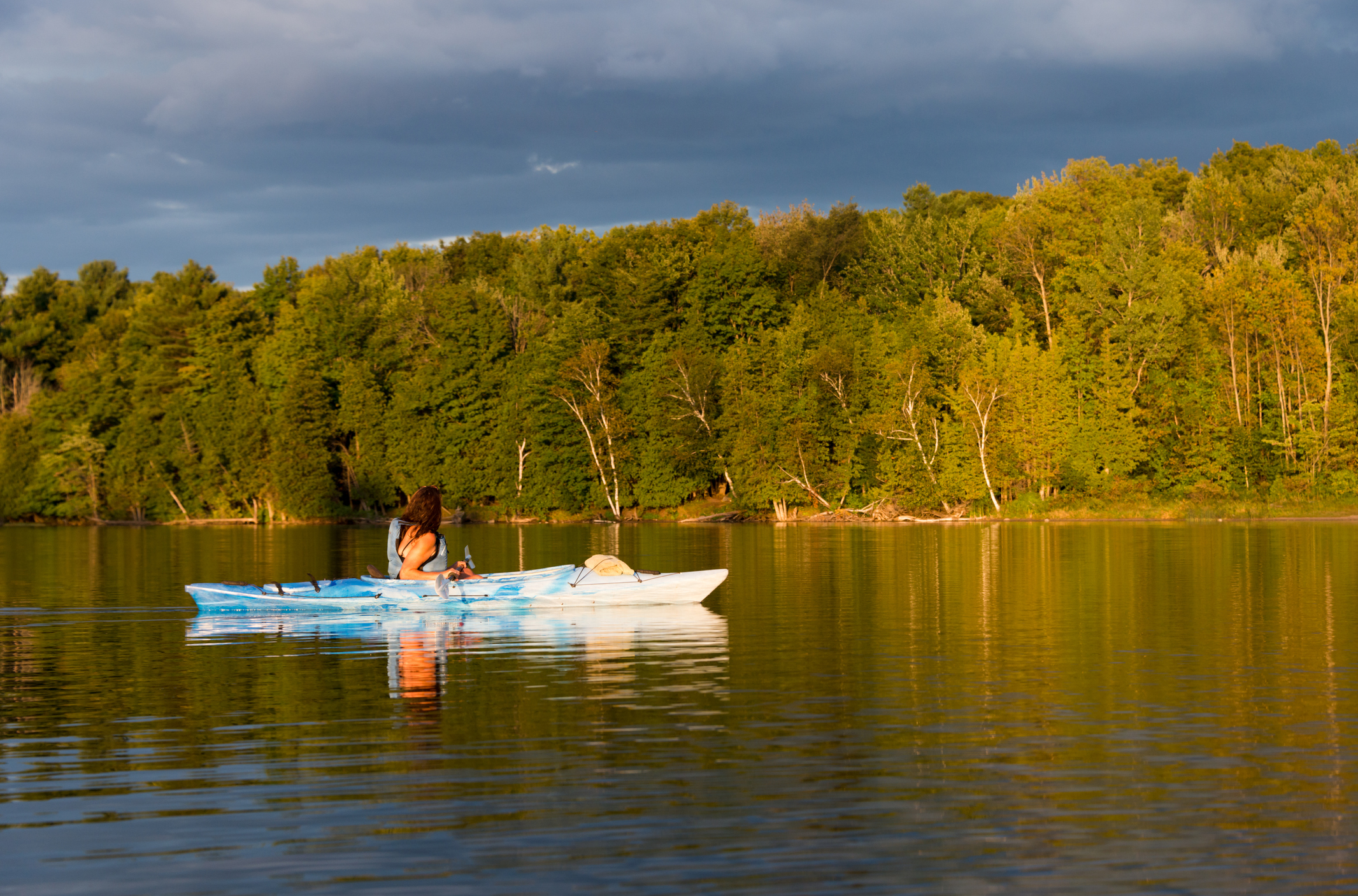 Woman kayaking on a northern lake just before sunset with golden light hitting the shoreline forest