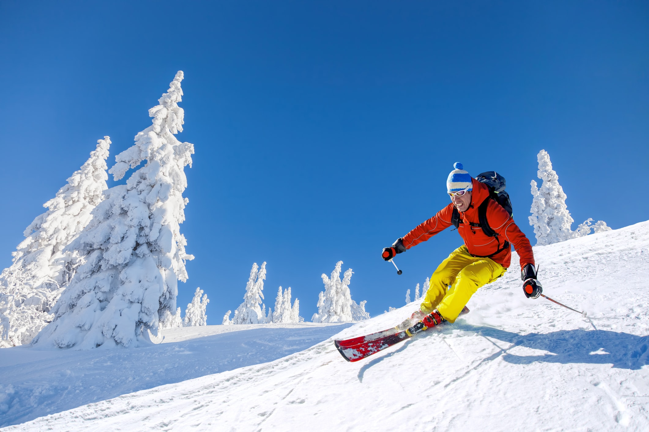 Downhill skiier on smooth white slopes.