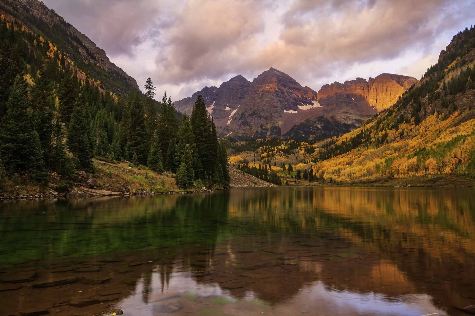 Gold and scarlet hues adorn the sides of rugged mountains and are reflected on a lake.