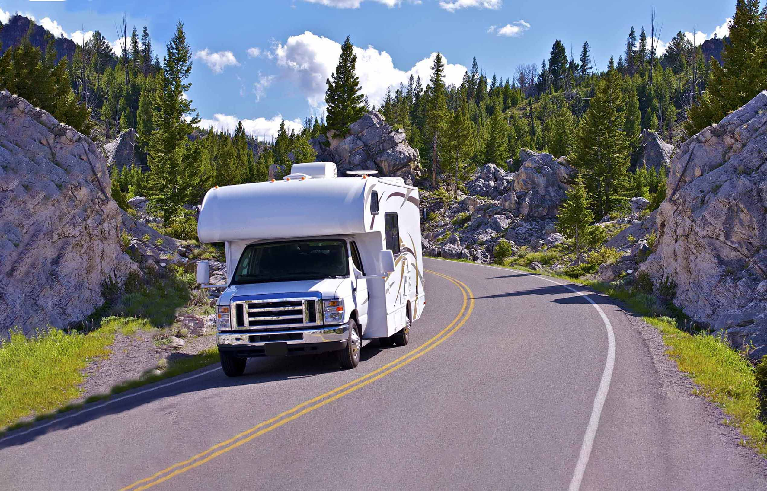 RV taking the curve of a mountain road.