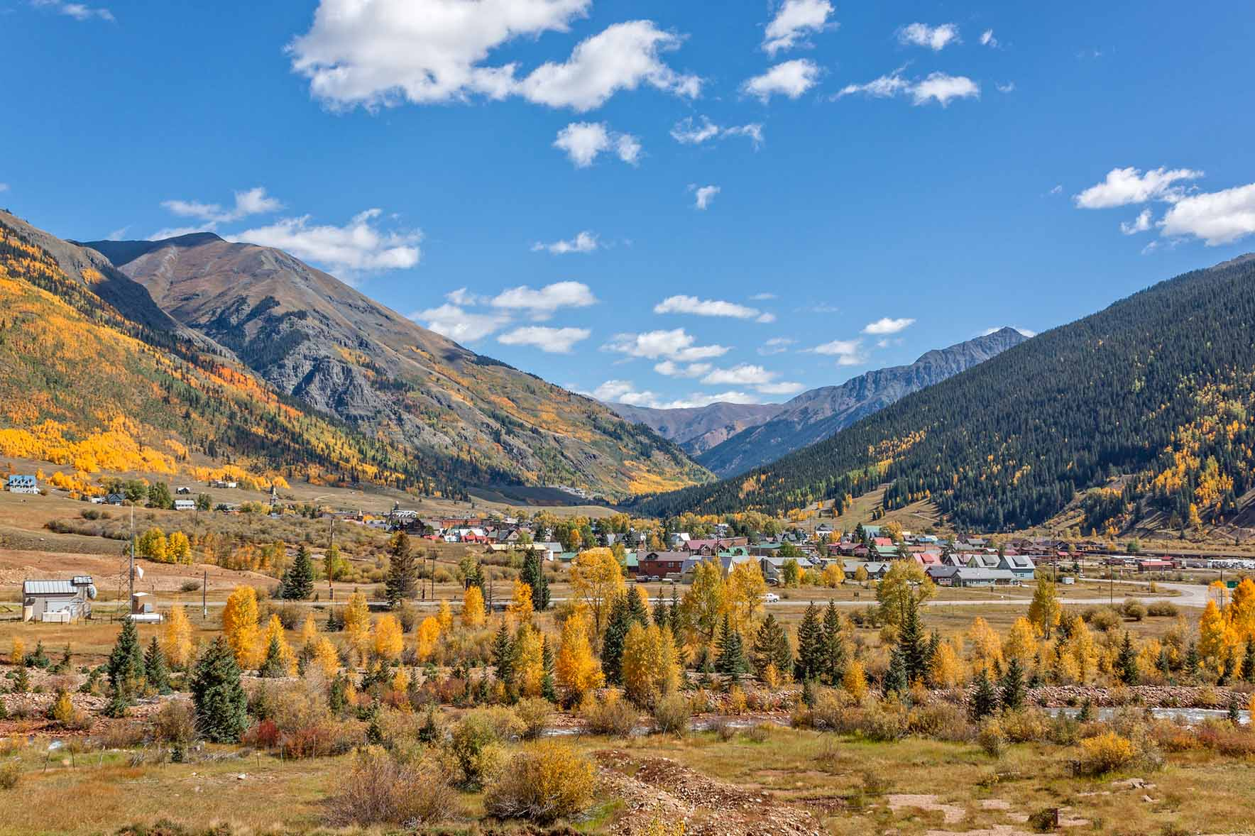 A small town nestled in a fall mountain landscape.