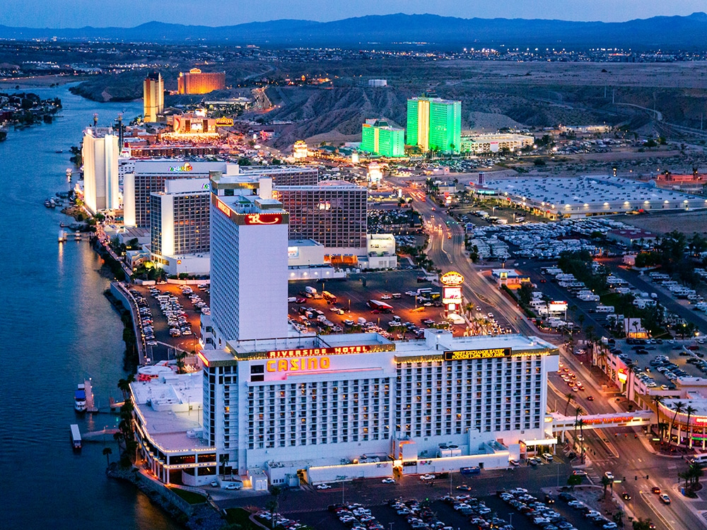 Aerial view of casinos awash in neon light at dusk.