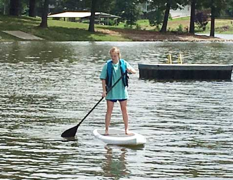 Girl with oar on a paddleboard.