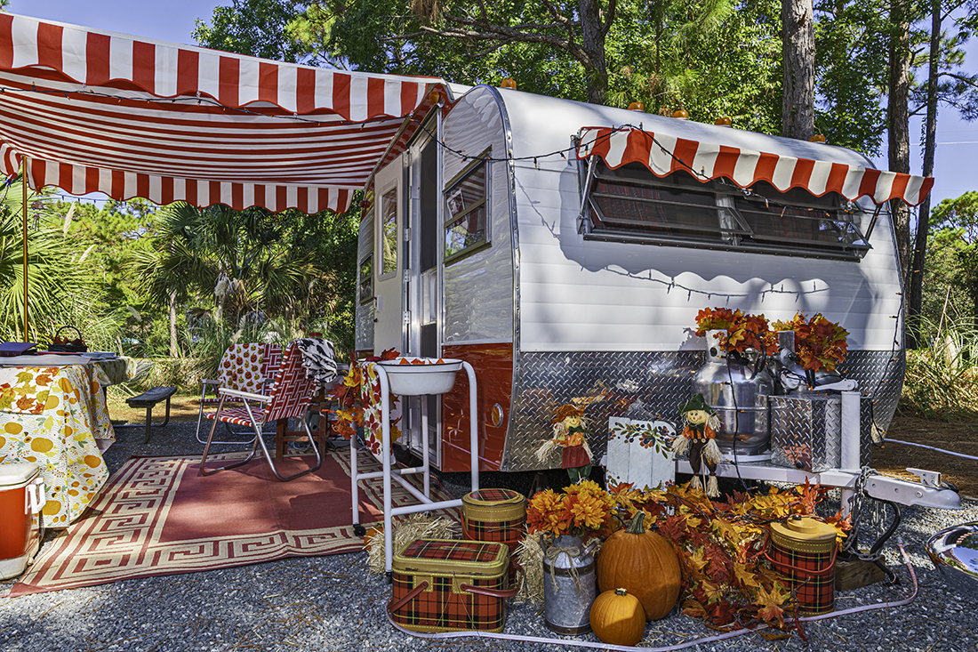 Colorful classic trailer surrounded by pumpkins and other fall decor.