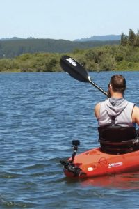 Man kayaks on a lake with wooded banks.
