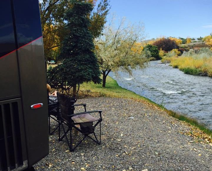 RV travelers relaxing on a waterfront campsite with motorhome.