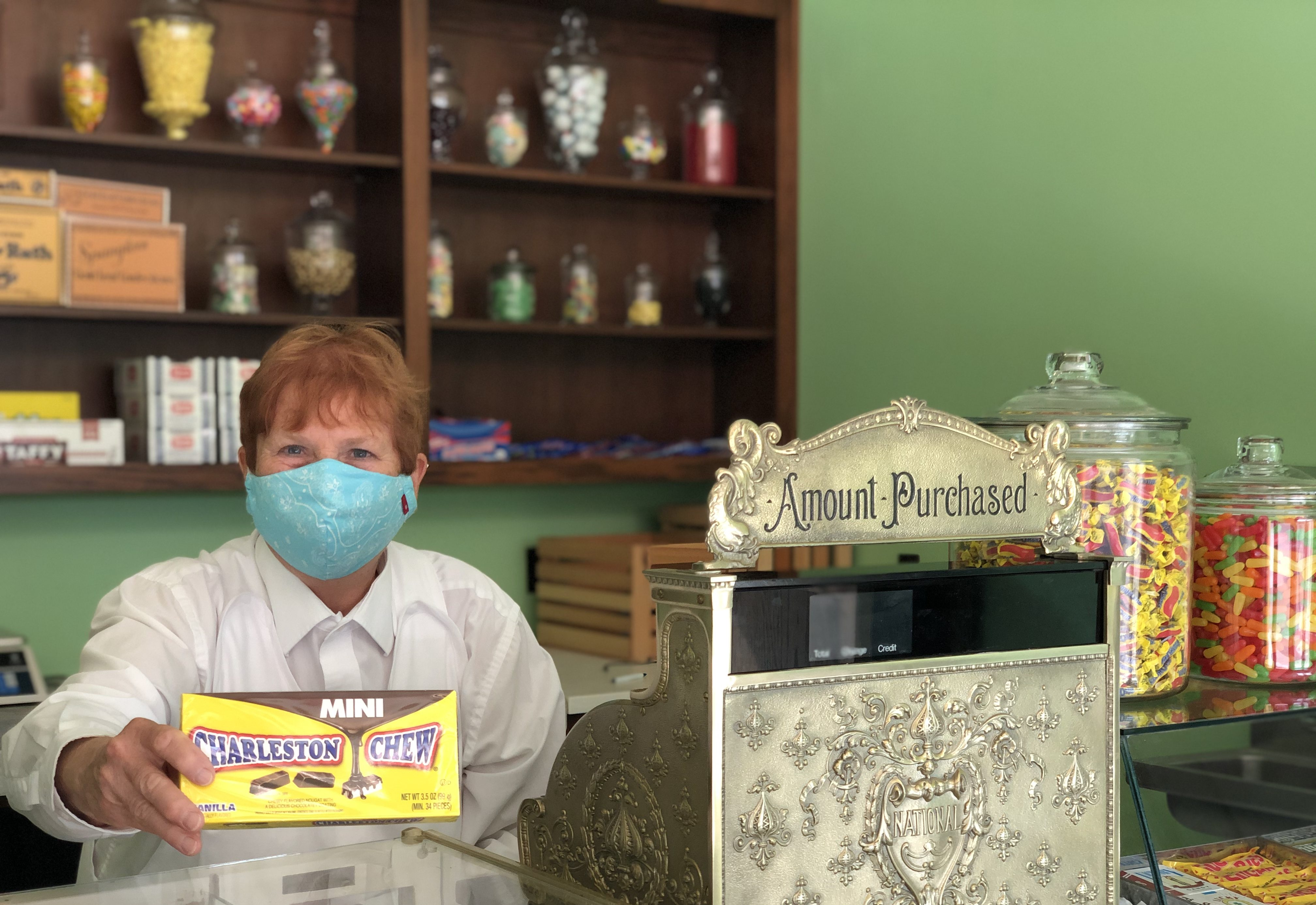 A cashier holds out a Charleston Chew.