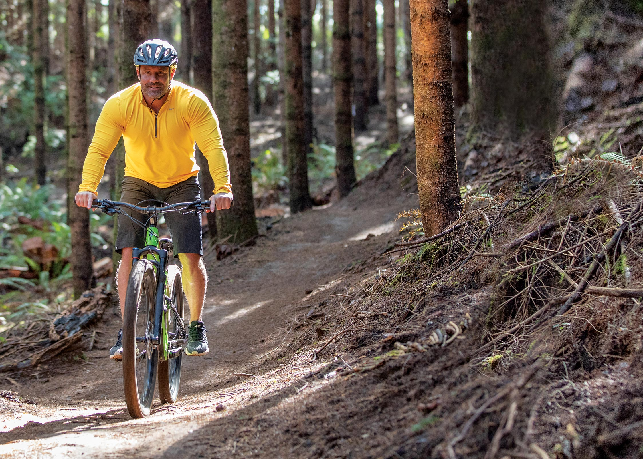 A man in yellow shirt rides bike down a wooded trail.