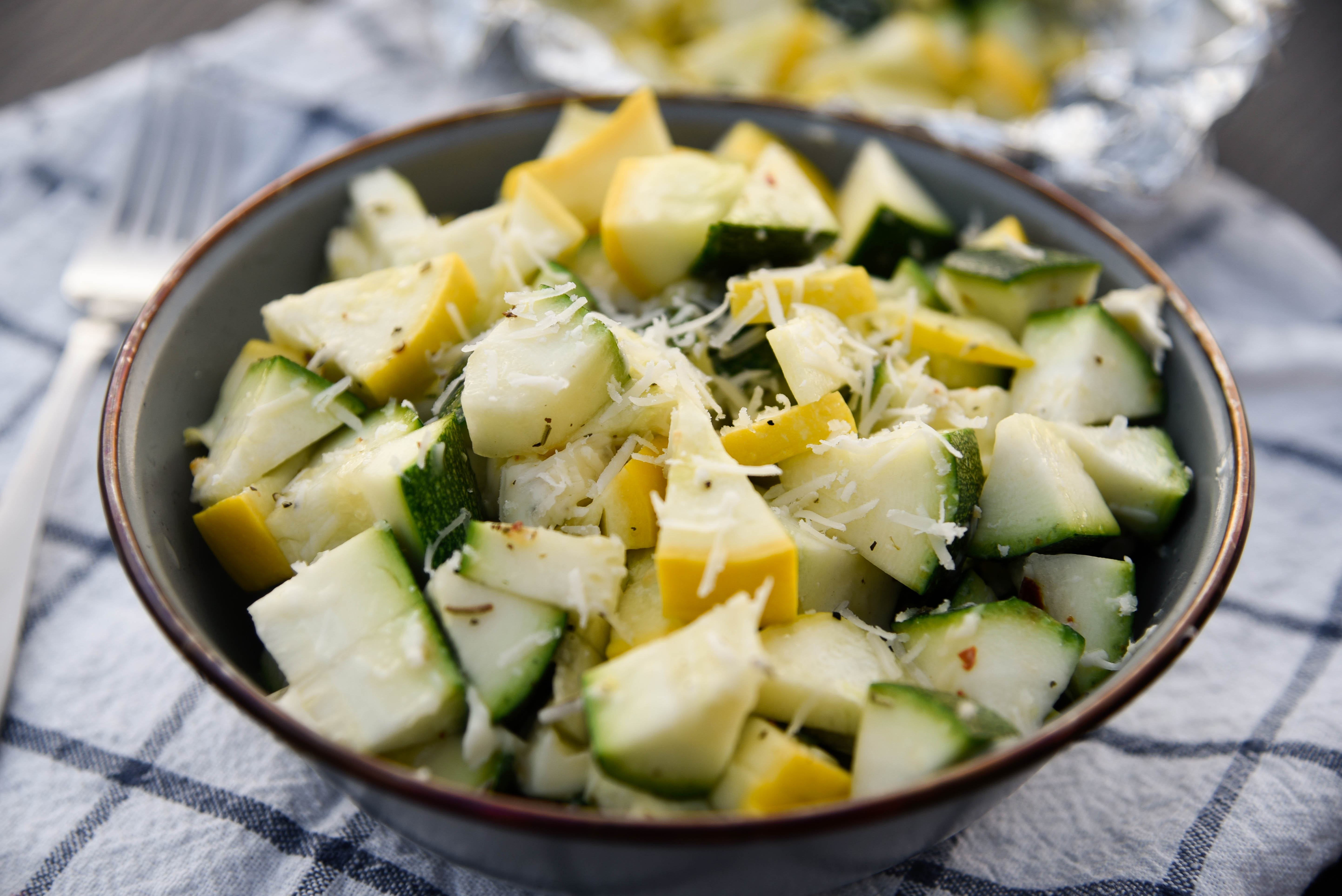 Bowl of Zuchini topped with cheese.