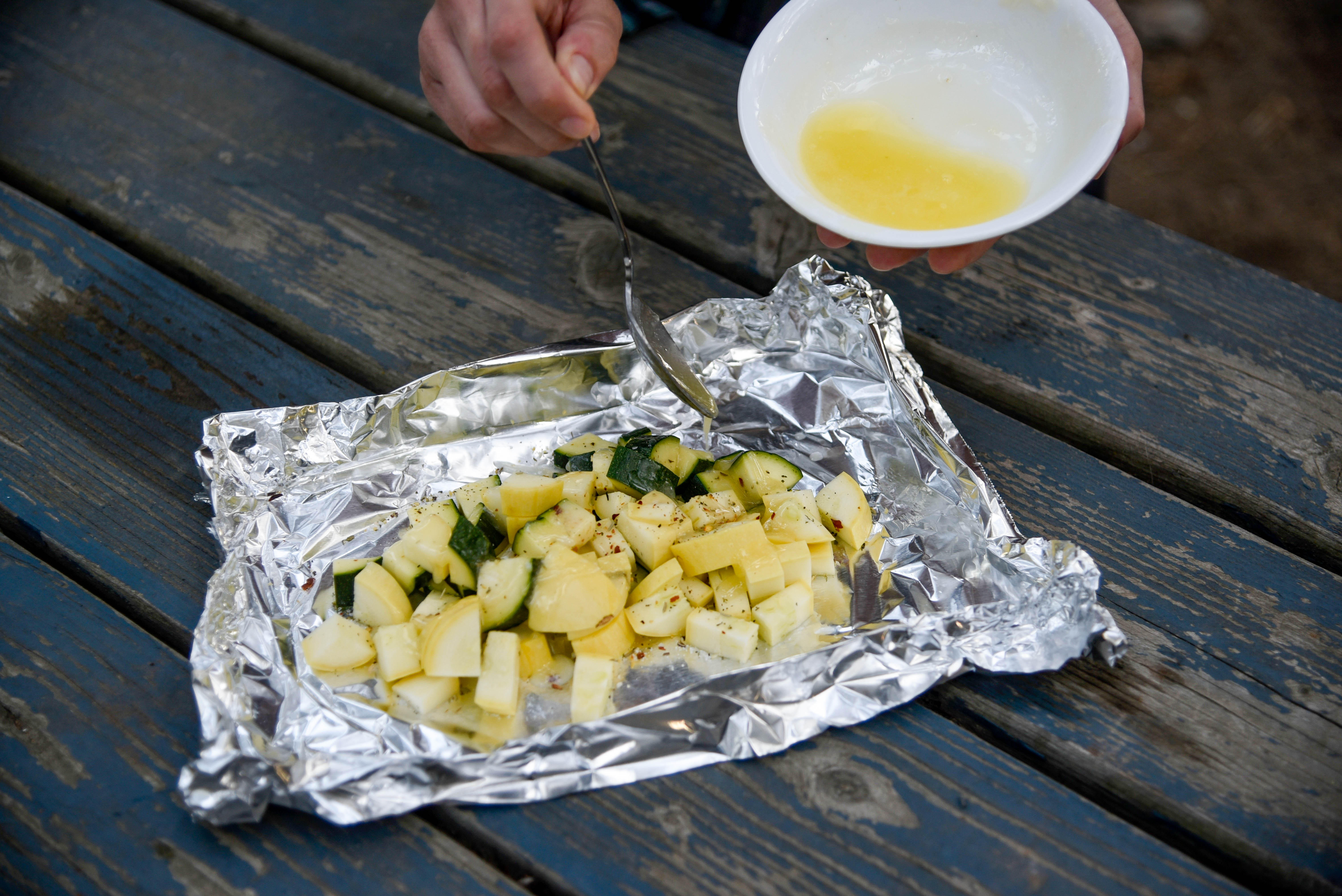 Pouring butter on chopped zucchini