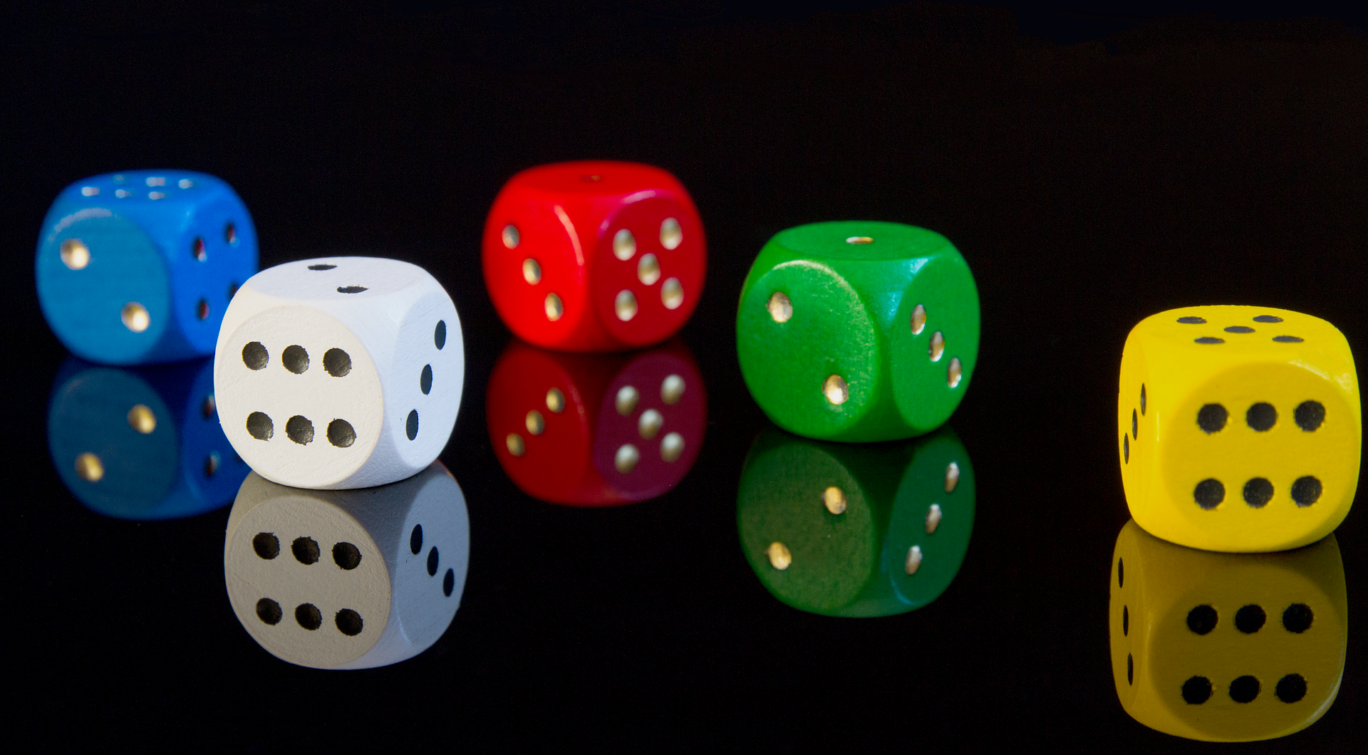 Muticolored dice on a black reflective background.