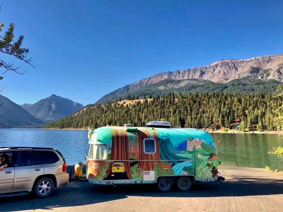 Colorful Airstream trailer parked next to Wallowa Lake with view of mountains