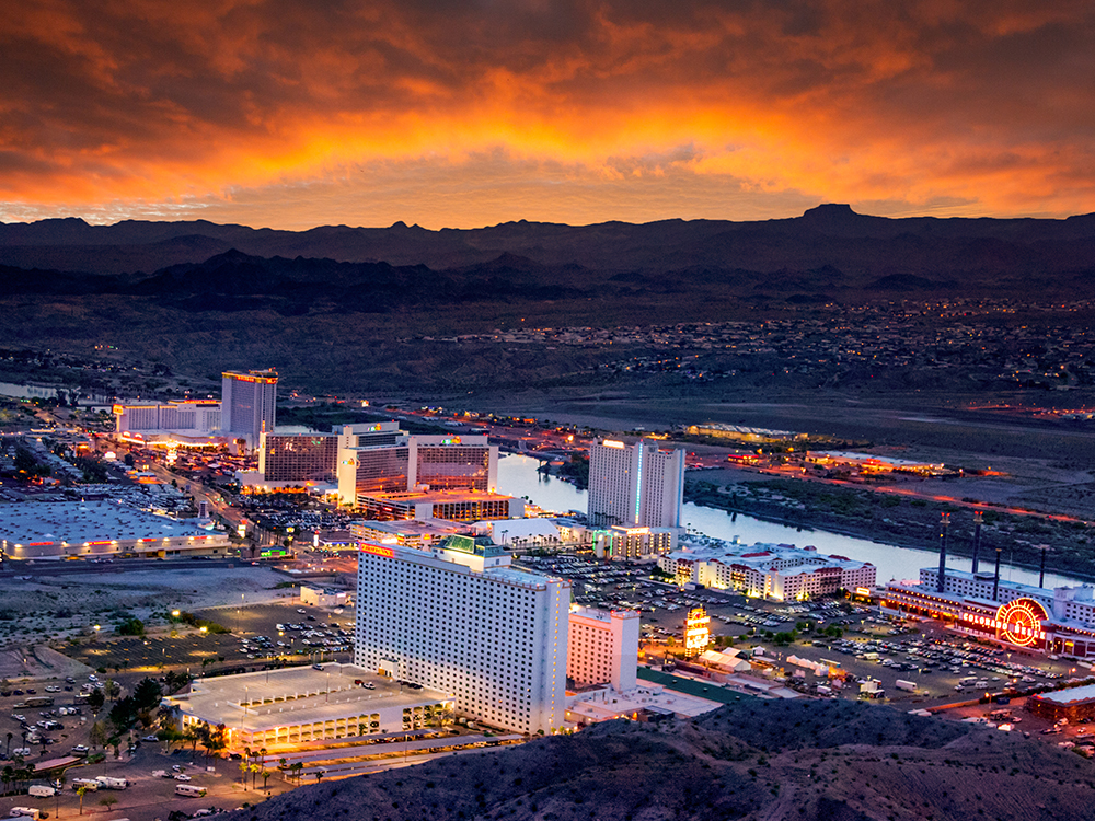 A dusk view of high-rise casinos overlooking a river.