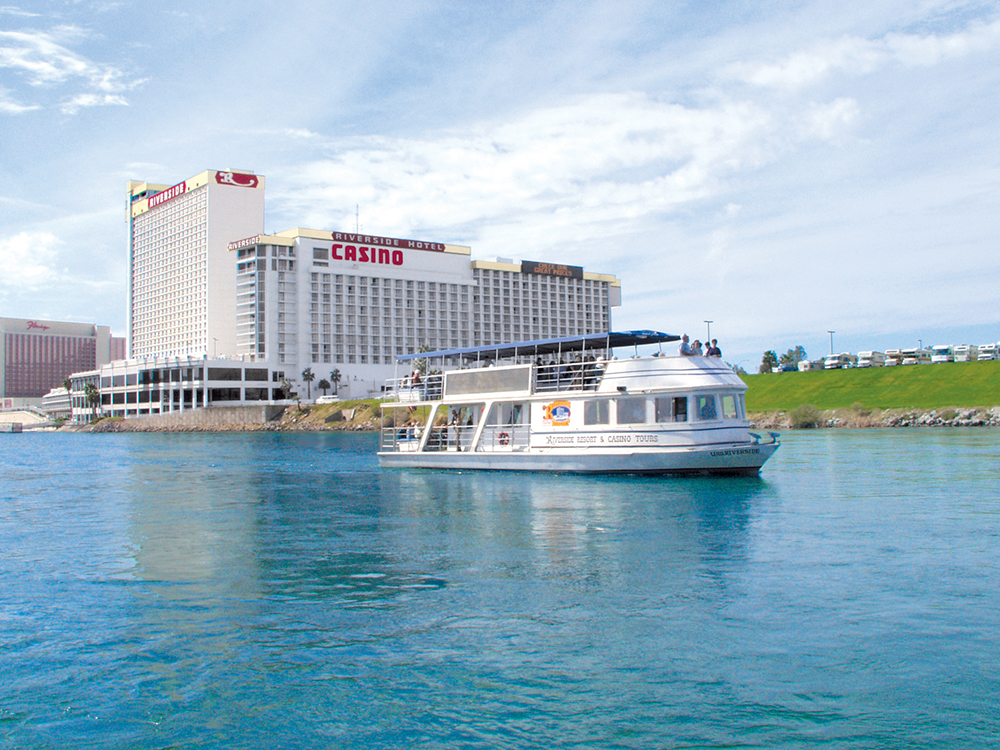 A tour vessel plies a river with casino in background.