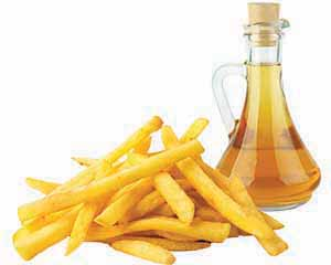 A pile of fries and glass bottle of vinegar on white background.