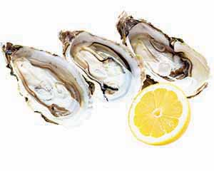 Three oysters with half of a lemon.