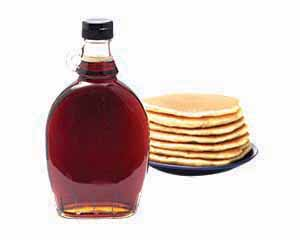 Bottle of maples syrup with pancakes in background.
