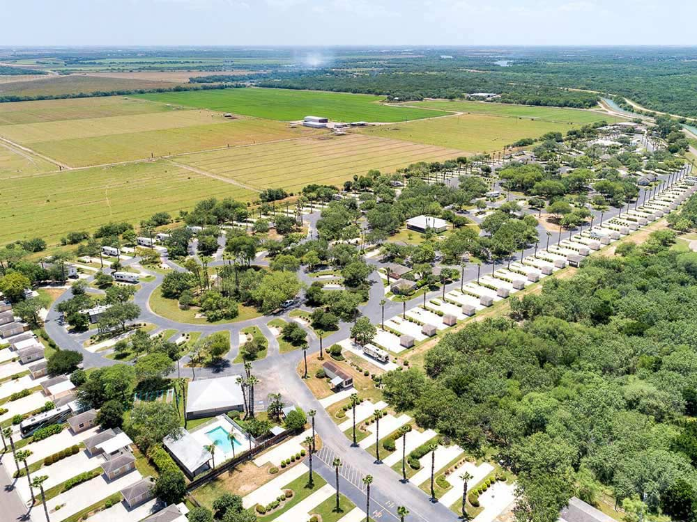 Aerial view of RV park surrounded by green fields and woods.
