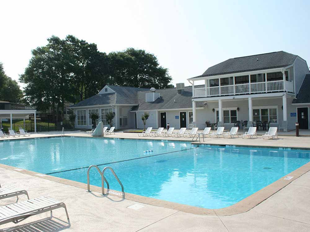 A big pool with stately clubhouse in background.