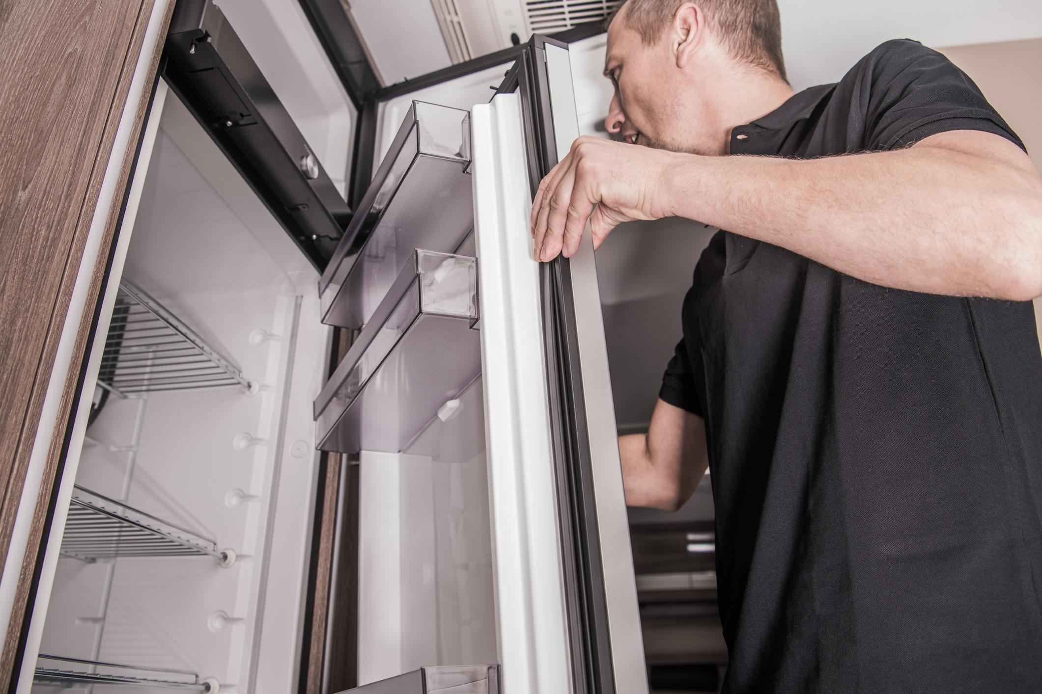 Man inspects an RV fridge.