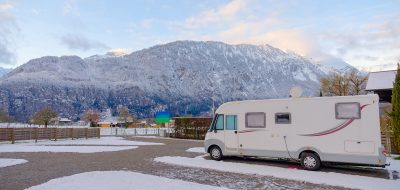 An RV in a snow-covered ccampground.