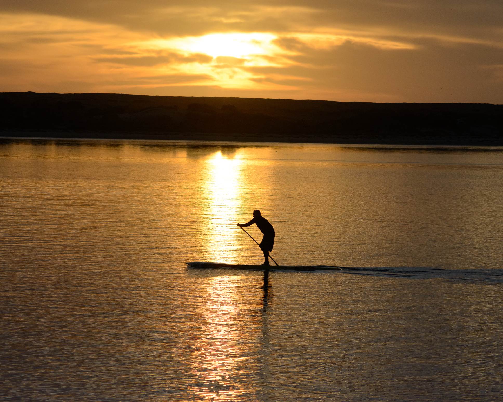 A man paddleboarding during sunset.