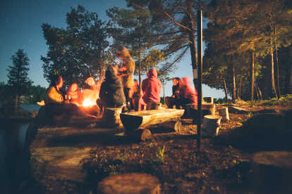 Young adults and kids around a campfire next to lake