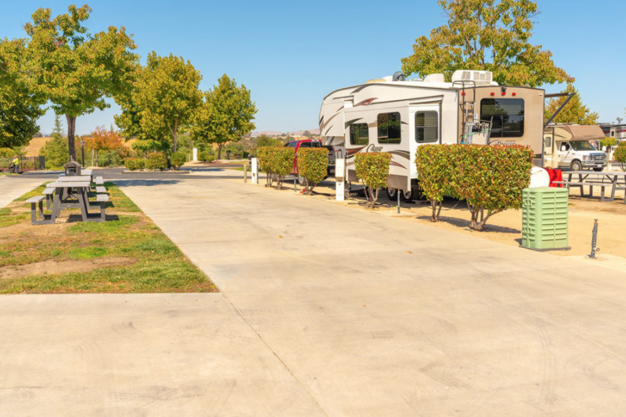 An RV parked near a patio and picnic table.