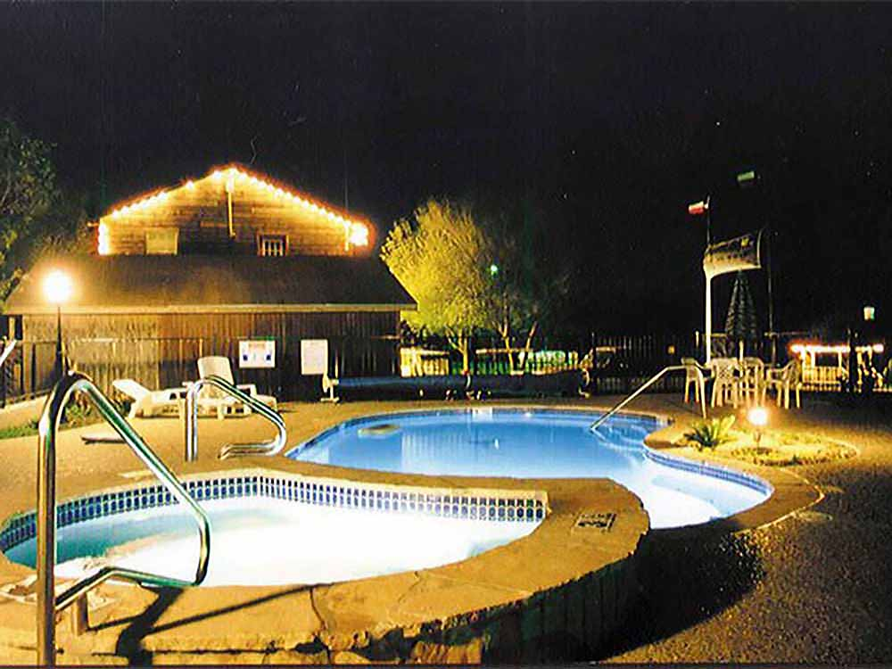 A hot tub adjacent to a pool under an evening sky illuminated by bright lights.