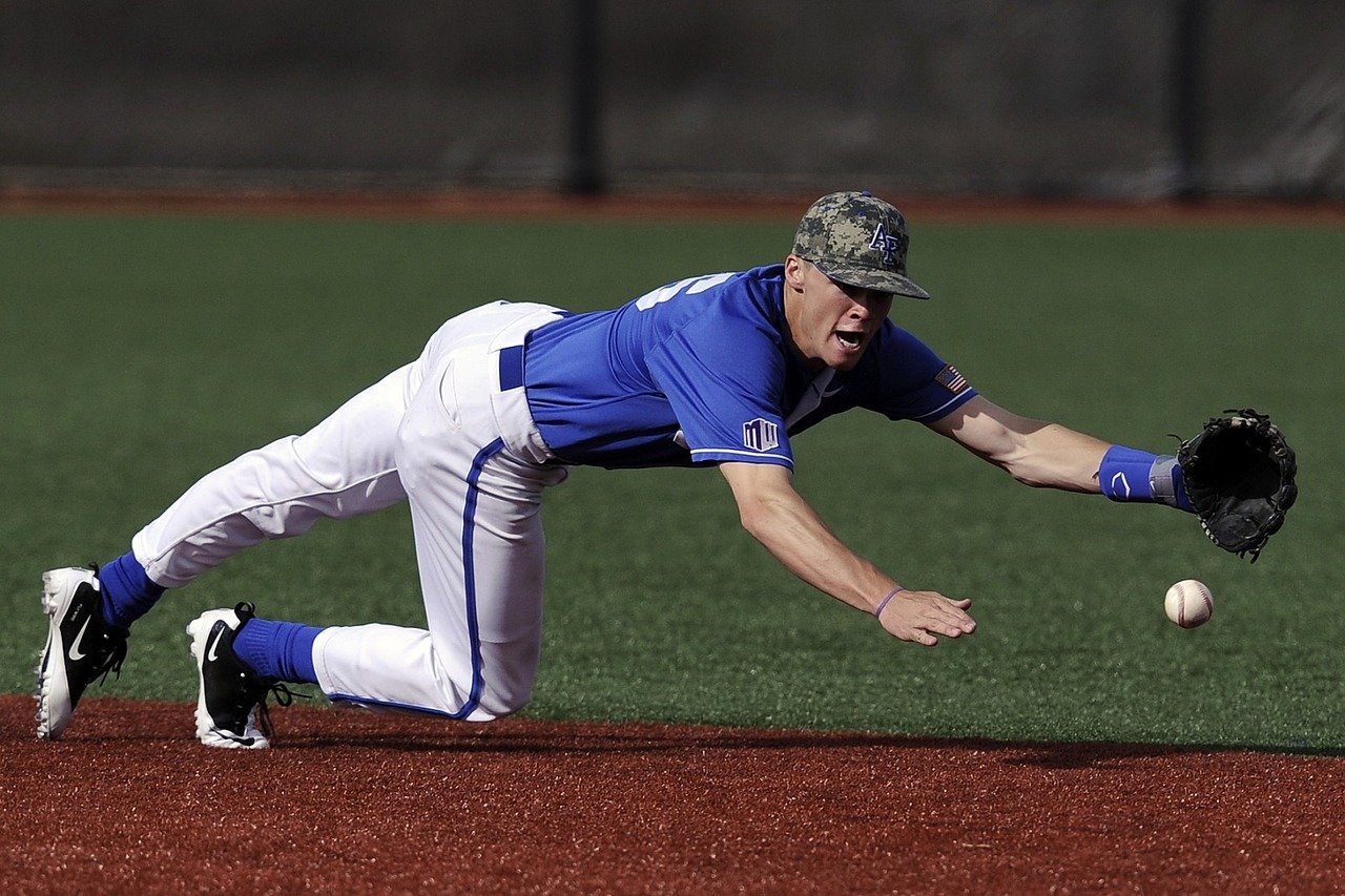 A baseball player in a blue Jersey dives for a ground ball.
