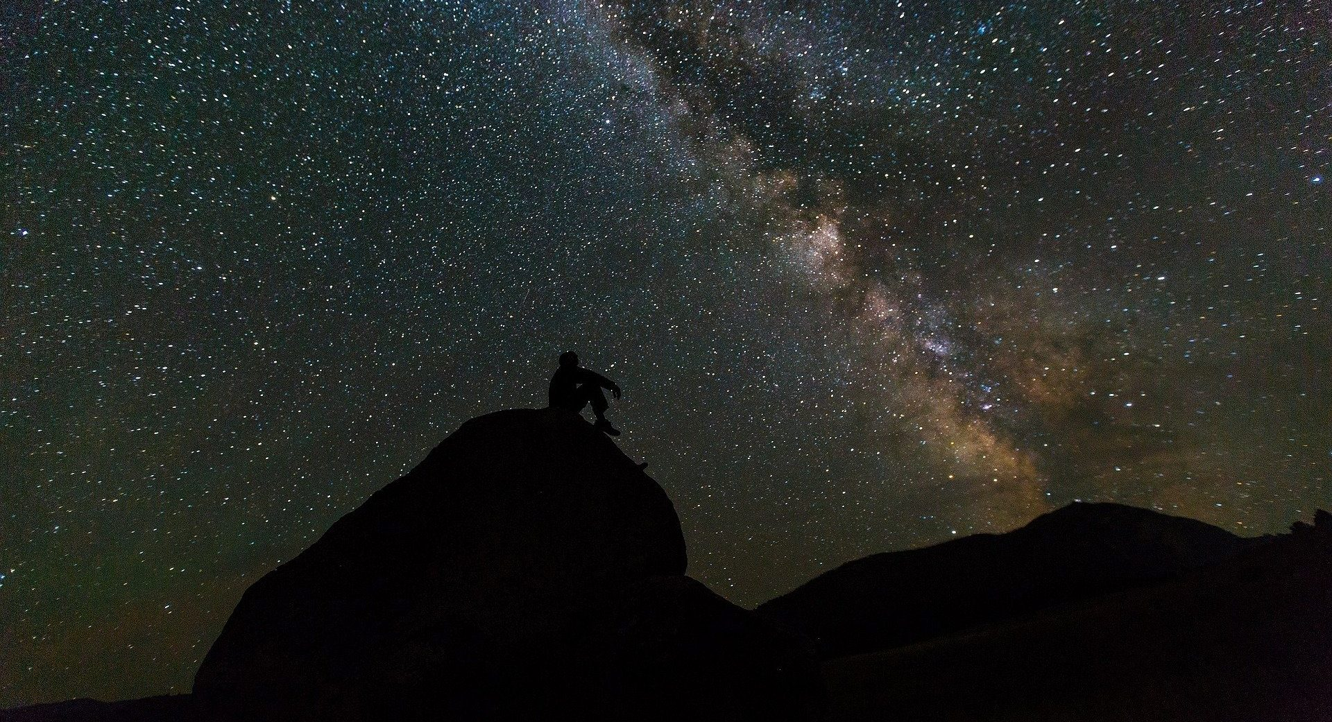A lone star watcher gazes up at a dense band of distant suns.