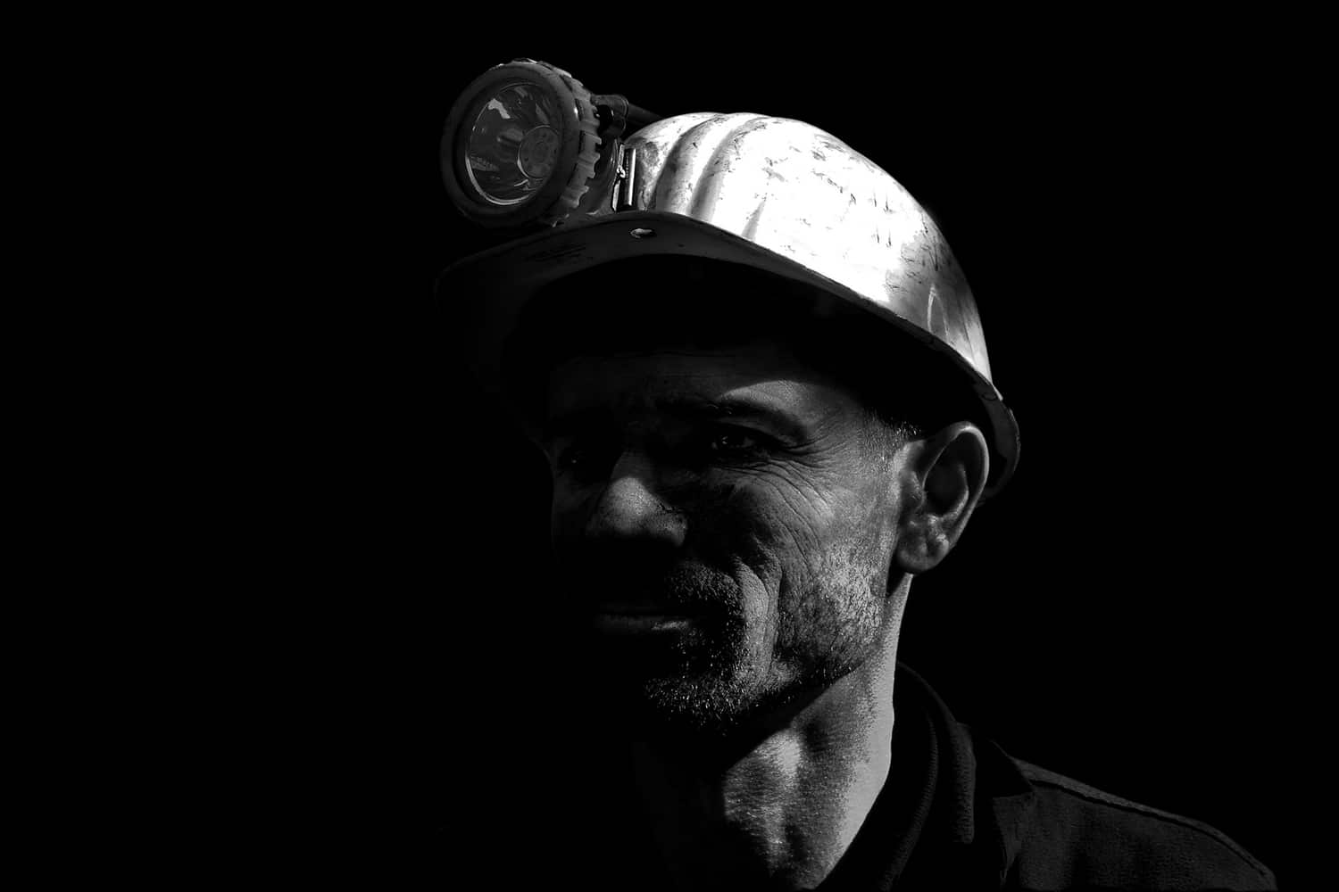A miner in the dark in a black-and-white photo.