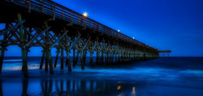 A pier stretches into the ocean at dusk.