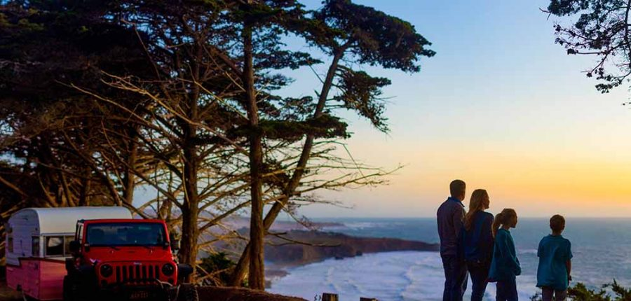 A family watches sunset from a cliff.