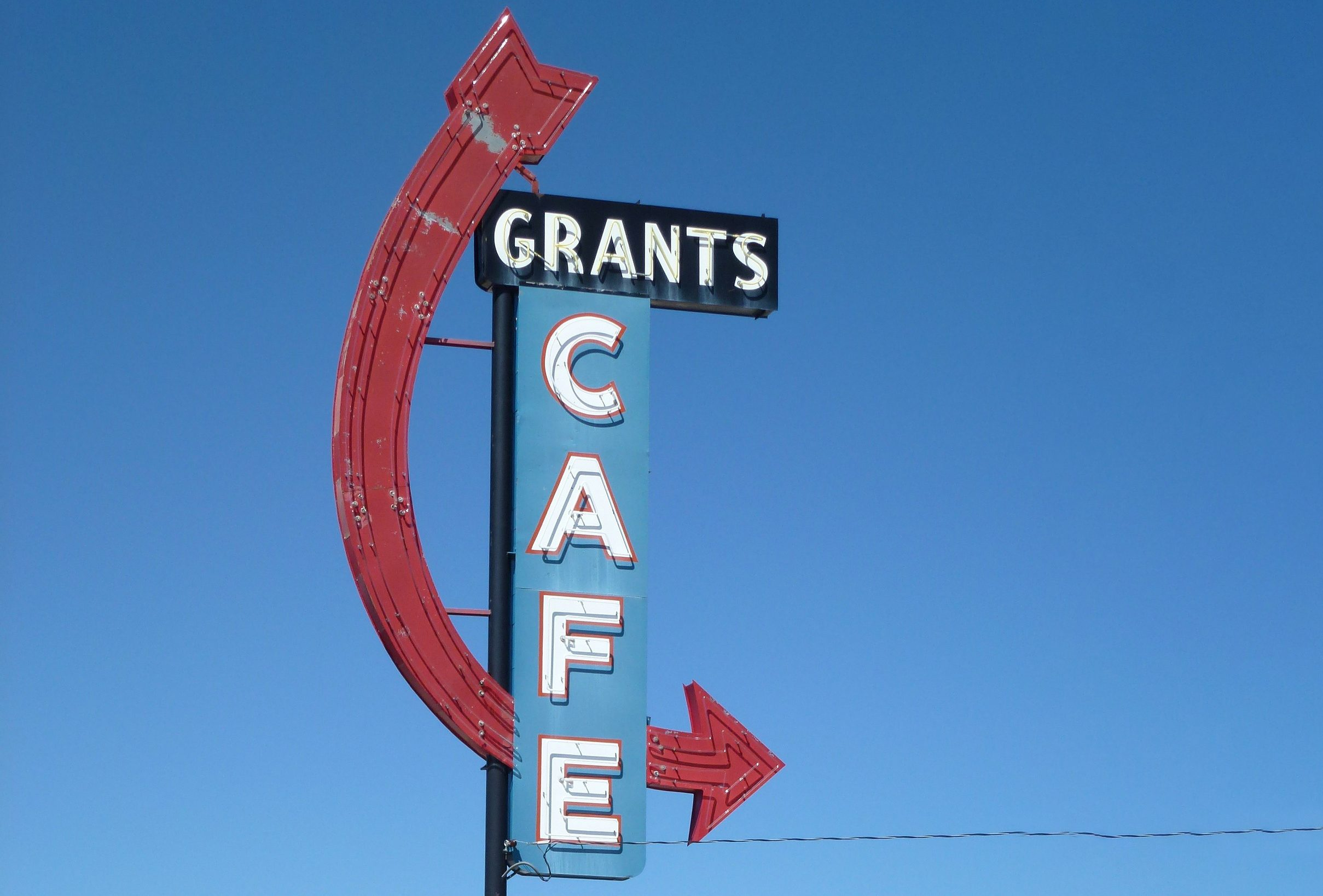 A 50s-style sign pointing out the location of a cafe.
