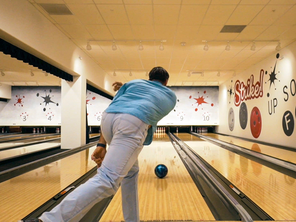 "A man throws a bowling ball down an alley with vibrant, colorful ""strike"" sign nearby."