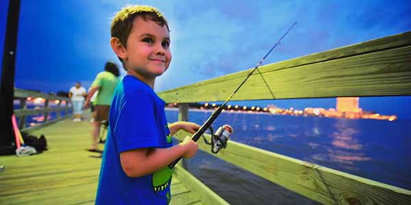 A toddler fishes on a pier in Biloxi, Ms.