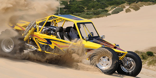 Dune buggy throwing sand in turn
