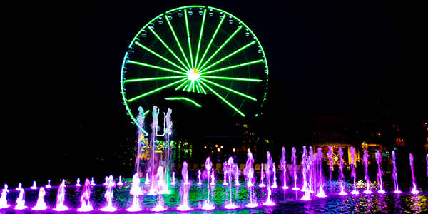 A ferris wheel and water fountain lit up at night