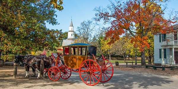 A horse drawn carriage along the street in Williamsburg in the Fall.