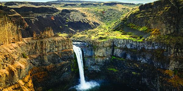 Waterfall cascades down a sheer cliff.