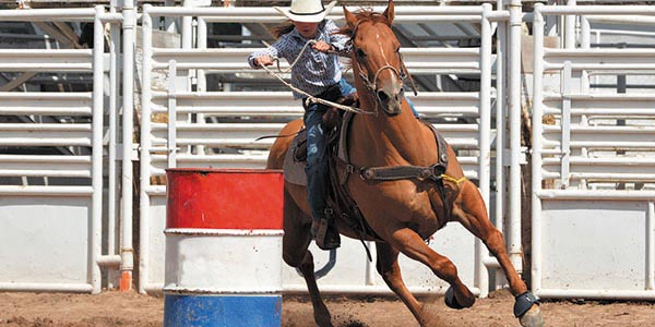 Cowgirl with lasso in barrel racing competition