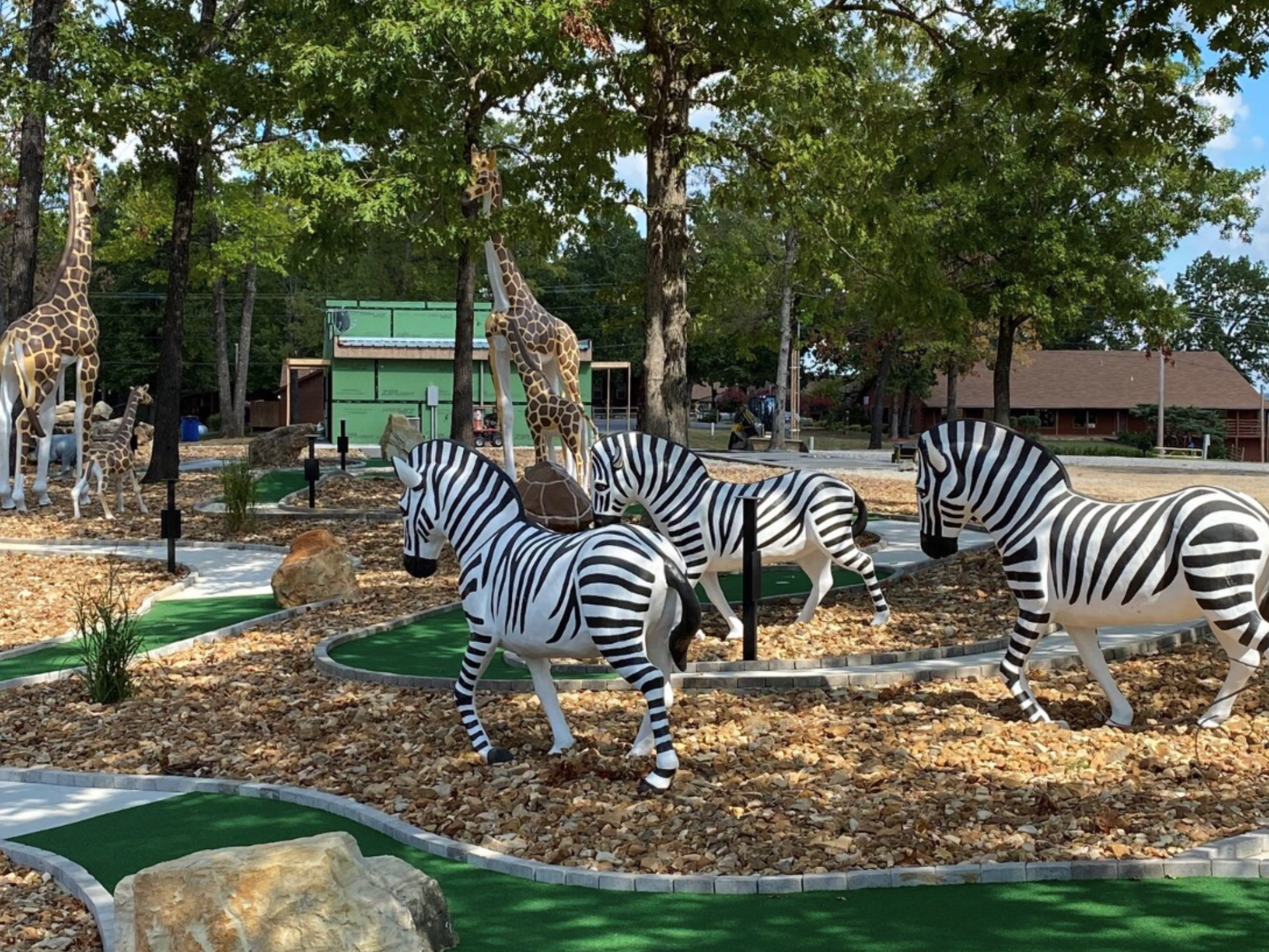 A playground with zebras and giraffe statues