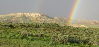 A rainbow arches over terrain in Fossil Butte.
