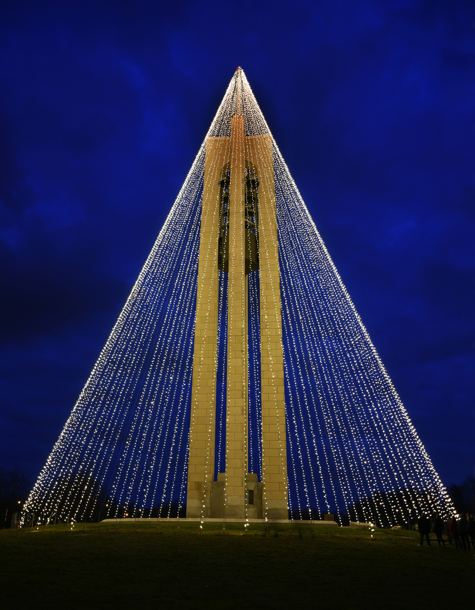 A tower bedecked with long strands of light.