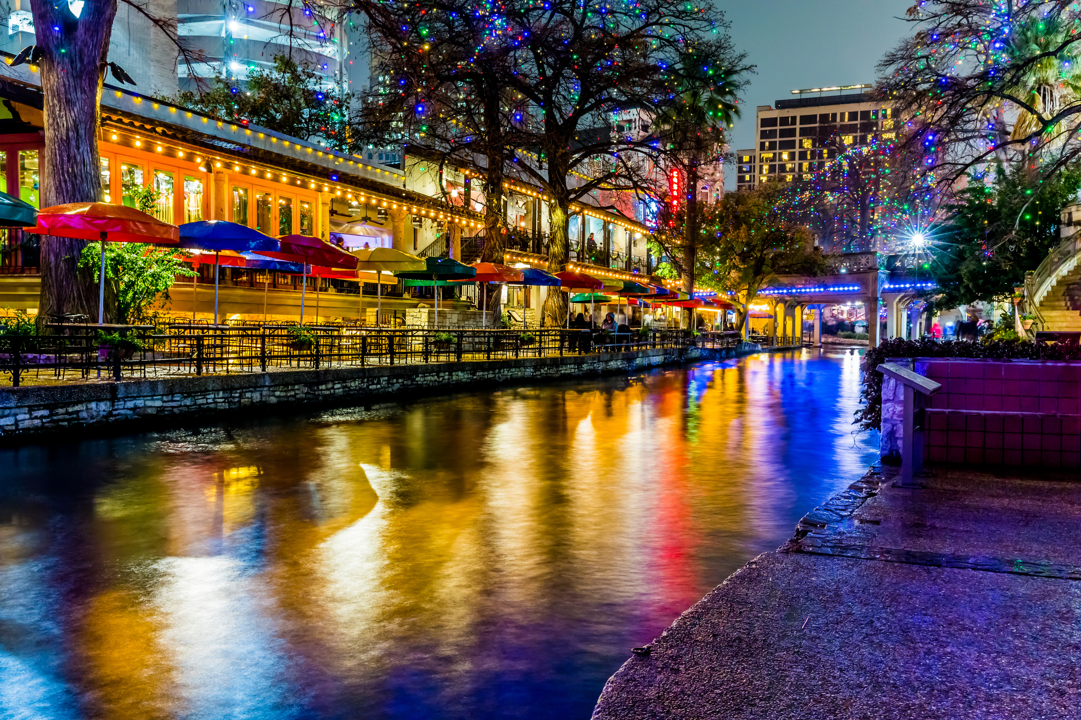 River lined with colorful umbrellas and Christmas lights in the evening.